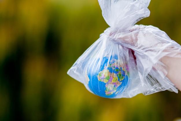 Menschliche hand hält den planetenerde in einer plastiktüte