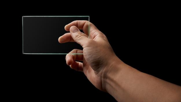 Menschliche hand hält ein transparentes glas auf einem schwarzen hintergrundplatz für text