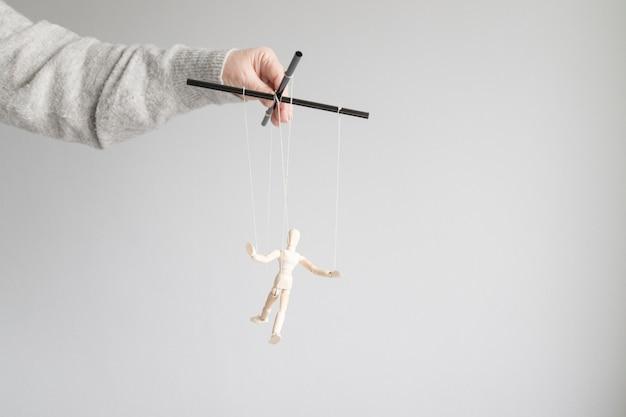 Menschliche hand hält eine holzpuppe auf der wäscheleine auf einem grauen hintergrund mit platz für text. power metapher konzept