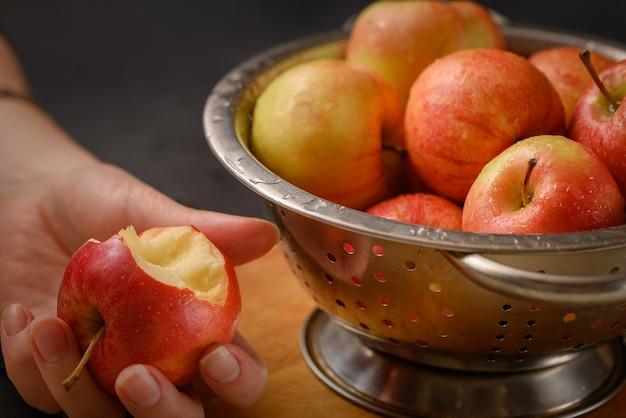 Menschliche hand hält gebissenen apfel, der von der metallschale voller roter reifer äpfel genommen wird. gesundes essen. apfelkuchen-zutaten. zu hause kochen