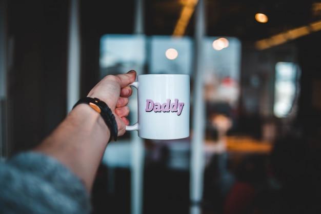 Menschliche hand hält kaffeetasse