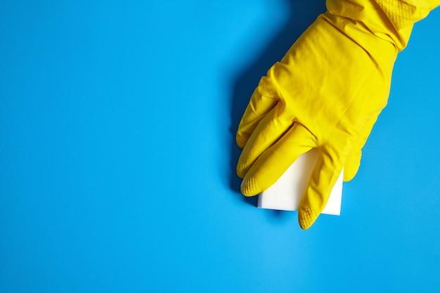 Menschliche hand im gelben handschuh hält einen weißen melaminschwamm auf blauem hintergrund mit kopienraum
