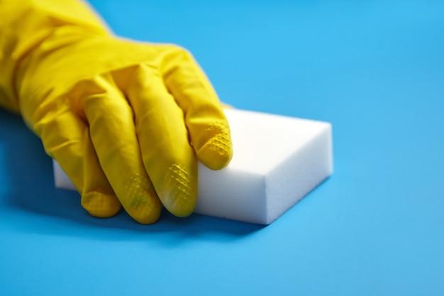 Menschliche hand im gelben handschuh hält einen weißen melaminschwamm auf blauem hintergrund