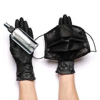 Menschliche hand im schutzhandschuh, der gesichtsmaske hält