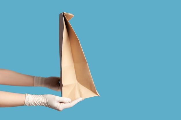 Menschliche hand in chirurgischen handschuhen, die papierpakete mit lebensmitteln halten und herstellen. sicheres konzept für die lebensmittellieferung