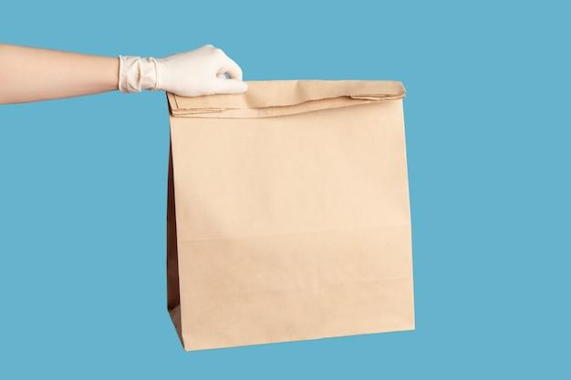 Menschliche hand in weißen handschuhen, die papierpakete mit essen halten und herstellen. sicheres lebensmittellieferkonzept.