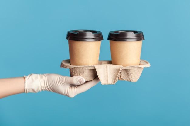 Menschliche hand in weißen op-handschuhen, die eine tasse heißen becher zum mitnehmen in der hand halten und zeigen.