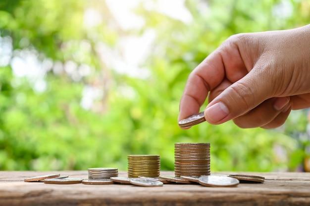 Menschliche hand legte eine münze in den stapel von münzen finanzkonzept und geschäftswachstum