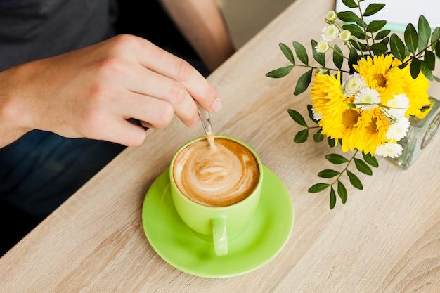 Menschliche hand mit einem löffel, um den kaffee im café zu rühren