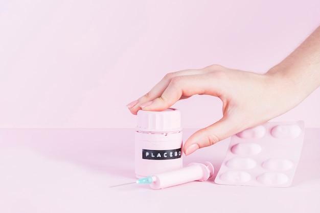 Menschliche hand über placeboflasche mit spritze und pillen blasen über rosa hintergrund