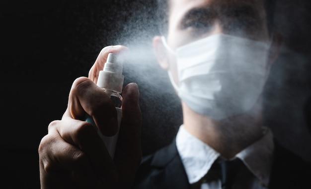 Menschliche hand und antiseptische sprühflasche auf dunklem hintergrund. kontrolle epidemischer präventionsmaßnahmen gegen coronavirus.