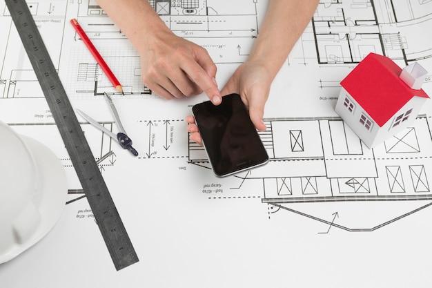 Menschliche hand unter verwendung des mobiltelefons über plan am arbeitsplatz