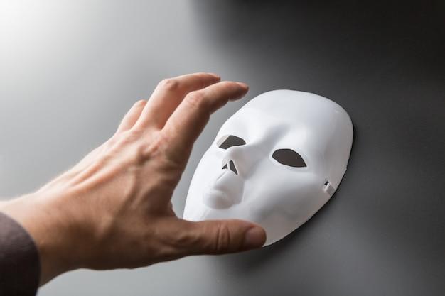 Menschliche hand versucht, theatermaske auf grau zu nehmen