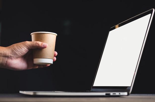 Menschliche hand vor laptop auf dem tisch mit leerem, modellbild des bildschirms