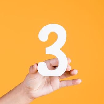 Menschliche hand, welche die nr. 3 gegen einen gelben hintergrund hält