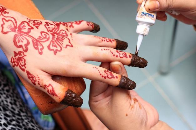 Menschliche hand wird mit henna-tattoo verziert