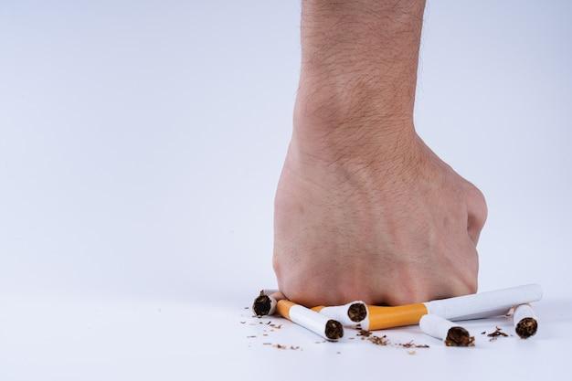 Menschliche hand zerschmettert haufen zigaretten