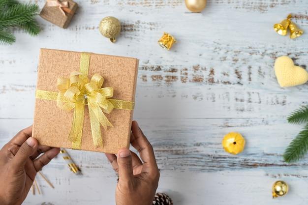 Menschliche handgriff weihnachtsgeschenkbox mit weihnachtsdekorationshintergrund auf weißem brett