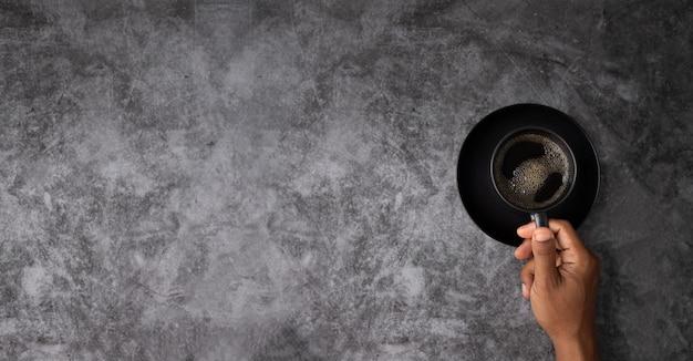 Menschliche handschwarze kaffeetasse mit copyspace auf schmutzzementwand-beschaffenheitshintergrund mit linkem kopienraum.