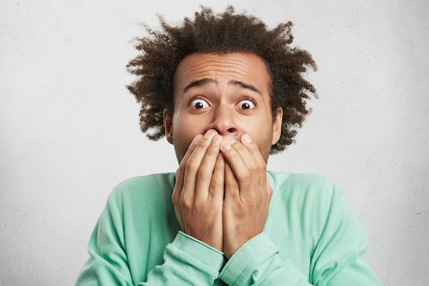 Menschliche mimik, emotionen und gefühle. afroamerikaner schaut mit abgehörten augen,
