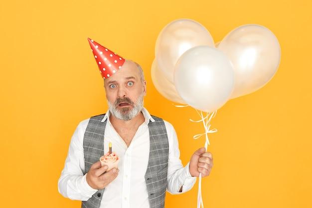 Menschliche mimik, emotionen und gefühle. bild des emotional schockierten älteren mannes mit grauem bart, der geburtstagskuchen und weiße heliumballons hält, erschreckten erschrockenen blick hat
