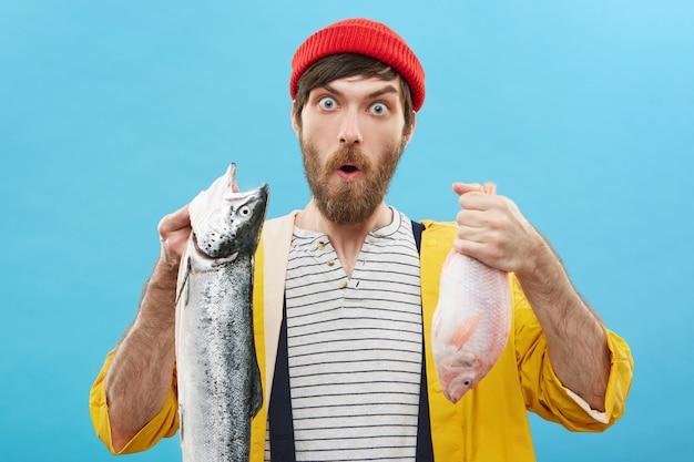 Menschliche mimik, emotionen und gefühle. lustiger erstaunter junger fischer, der roten hut und gelben regenmantel trägt, der gegen wand mit zwei fischen aufwirft, überrascht mit feinem fang