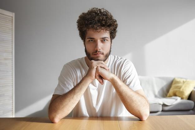 Menschliche mimik. porträt eines ernsthaften jungen unrasierten mannes mit lockigem haar, das kinn auf seinen händen hält und mit nachdenklichem blick, über etwas nachdenkend, drinnen posierend