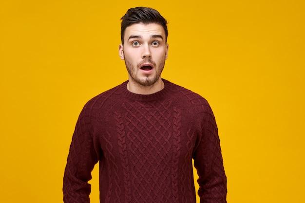 Menschliche mimik und emotionen. schockierter emotionaler junger mann in gestricktem pullover, der vollen unglauben ausdrückt, überrascht von hohen verkaufspreisen auf schwarz