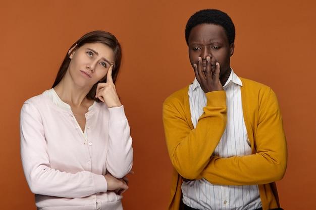 Menschliche mimik und körpersprache. frustrierte weiße studentin, die einen verwirrten gesichtsausdruck hat, aufschaut und versucht, sich an informationen zu erinnern, während ihr schwarzer männlicher gruppenmitglied neben ihr nachdenkt