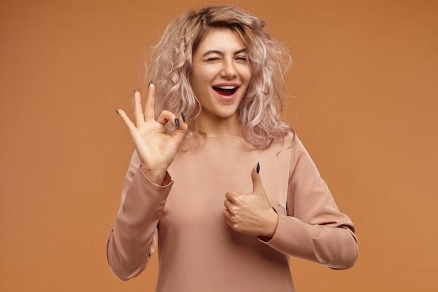 Menschliche mimik und körpersprache. horizontal der stilvollen modischen jungen kaukasischen frau mit unordentlichem rosa haar, das mit aufregung ausruft
