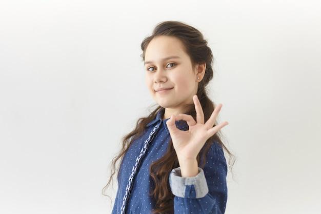 Menschliche mimik und körpersprachenkonzept. bild des positiven glücklichen teenager-mädchens mit langen dunklen haaren