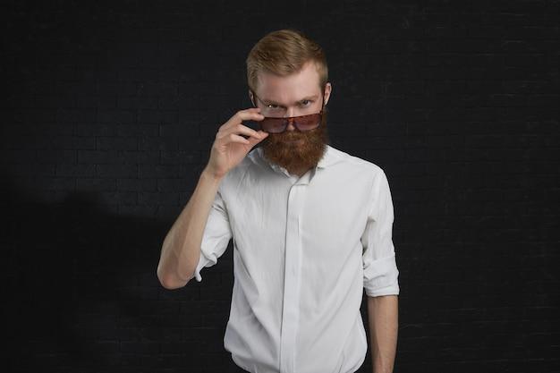 Menschliche mimik und reaktion. porträt eines mürrischen unzufriedenen jungen kaukasischen rothaarigen unrasierten mannes, der seine trendige sonnenbrille senkt