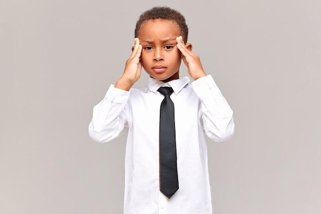 Menschliche reaktion, gefühle und haltung. frustrierter unglücklicher afrikanischer schüler in schuluniform, der tempel massiert, unter kopfschmerzen leidet und mit viel hausaufgabe gestresst ist