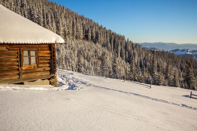 Menschlicher abdruckweg im weißen tiefen schnee, der zu kleine alte hölzerne verlassene schäferhütte im gebirgstal führt