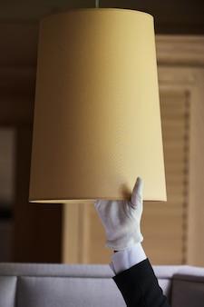 Menschlicher finger, der den qualitätshotelarbeiter überprüft, der staub unter der lampe überprüft