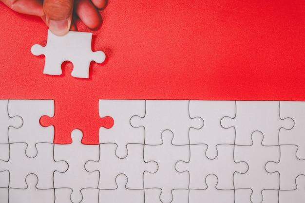 Menschlicher finger, der unvollendete weiße puzzleteile auf rotem hintergrund für endziel berührt