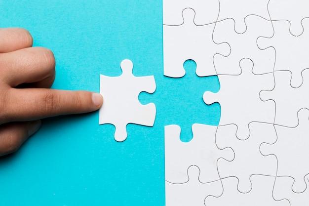 Menschlicher finger, der weißes puzzlespielstück auf blauem hintergrund berührt