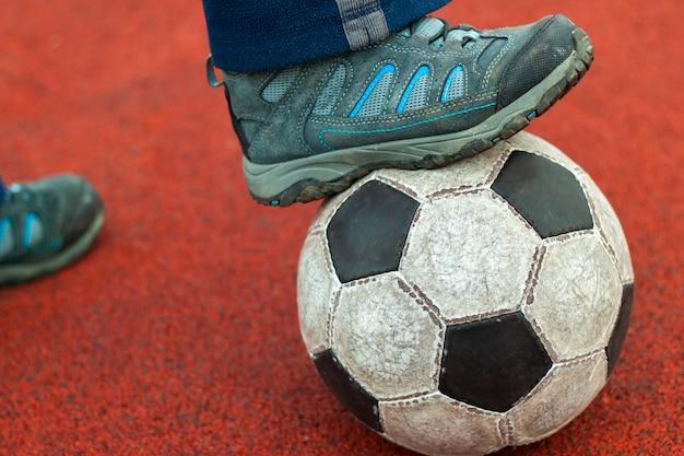 Menschlicher fuß in einem schmutzigen turnschuh auf einem alten fußball.