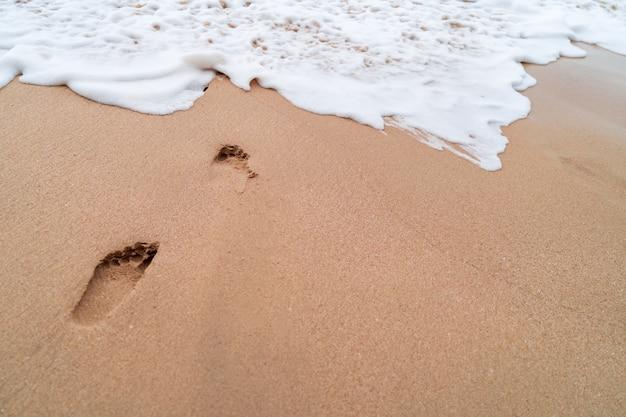 Menschlicher fußabdruck auf tropischem strandhintergrund des sandesommers.