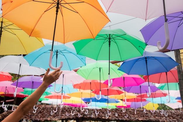 Menschlicher handgriff bunt erhöhen sie einen regenschirm.
