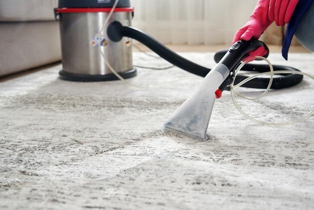 Menschlicher reinigungsteppich im wohnzimmer mit staubsauger zu hause