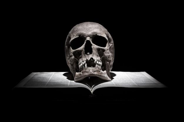Menschlicher schädel auf altem offenem buch auf schwarzem hintergrund unter lichtstrahl