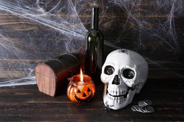Menschlicher schädel, dunkle glasflasche, münzen, schatulle und brennende kerze im glaskerzenständer in form von halloween-kürbis auf holzplankenoberfläche mit spinnweben. piraten-stillleben.