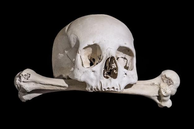Menschlicher schädel mit knochen auf schwarzem hintergrund