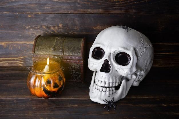 Menschlicher schädel mit spinnen, schatulle und brennender kerze im glaskerzenständer in form von halloween-kürbis auf holzbrettoberfläche