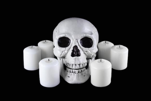 Menschlicher schädel unter weißen erloschenen kerzen im dunklen, gruseligen stillleben, altar.