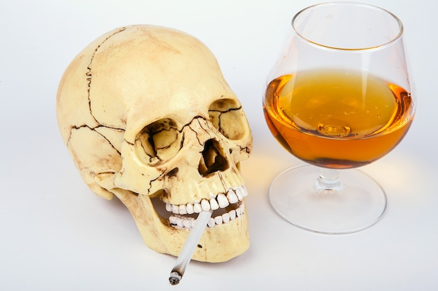 Menschlicher schädelkopf mit zigaretten und alkohol auf weißem hintergrund