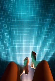 Menschliches bein, das hinunter swimmingpool-luftaufnahme hängt