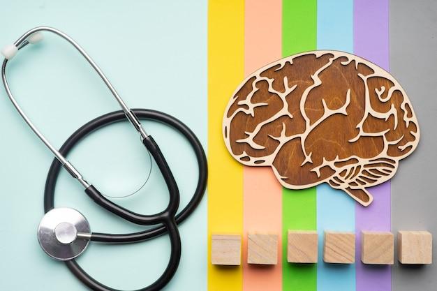 Menschliches gehirn mit stethoskop. sechs würfel, in die sie das wort autismus in ihrer schrift schreiben können.