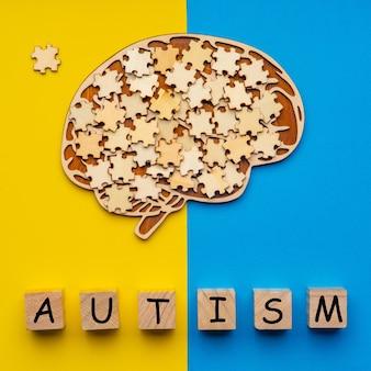 Menschliches gehirn mit verstreuten puzzleteilen auf gelb und blau. sechs würfel mit der aufschrift autismus.